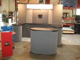 Modified FF-110 Intro Fabric Folding Panel System with Storage, Monitor Mount, Oval Counter, and Backlit Alcove Header -- Image 1