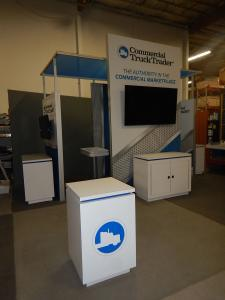 RENTAL: Custom Island with (2) 42� Monitors, (2) 70� Monitors, Custom Counters and Pedestals with Recessed Adjustable LED Accent Lighting, (2) RE-709 Charging Stations, and 10 ft. Square x 36 in. High Hanging Sign with Pillowcase Fabric Graphic
